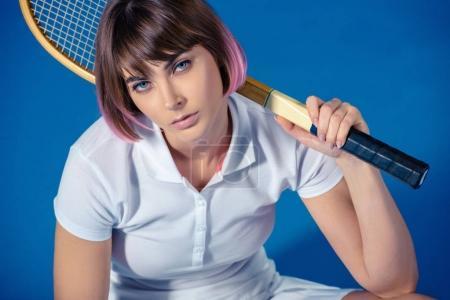 Photo pour Joueuse de tennis avec une raquette de tennis en regardant caméra isolée sur bleu - image libre de droit