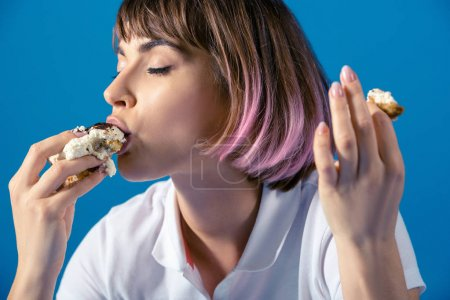 sexy Attractive woman eating piece of pie isolated on blue