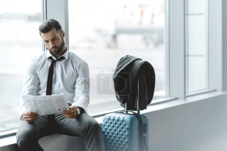 young businessman reading newspaper while waiting for flight at airport lobby