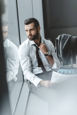 handsome young businessman waiting for flight at airport lobby and looking away