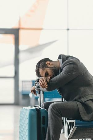 exhausted businessman sleeping at airport lobby while waiting for flight