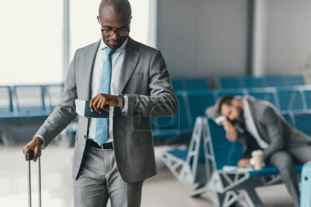 handsome businessman looking at watch while waiting for flight in airport lobby with sleeping man blurred on background