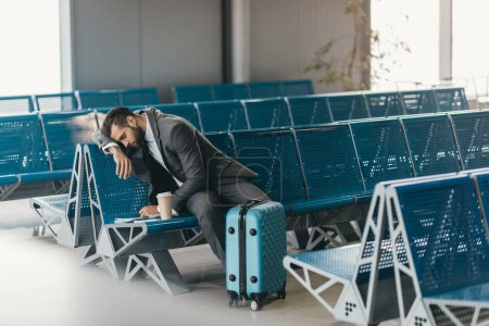 sleepy young businessman waiting for flight at airport lobby