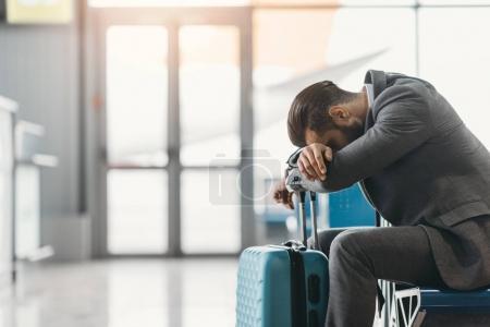 homme d'affaires fatigué dormir dans le hall de l'aéroport en attendant vol