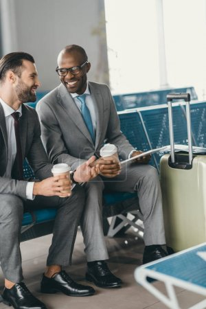 Photo for Business colleagues waiting for flight in airport lobby with coffee to go - Royalty Free Image
