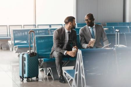 business colleagues waiting for flight in airport lobby