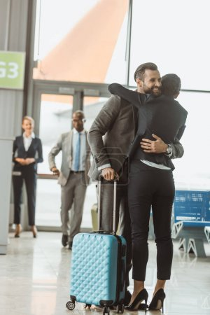 happy young businessman embracing with woman at airport