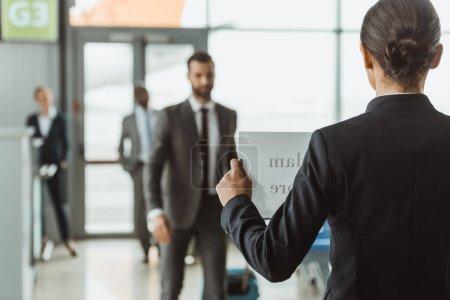 femme d'affaires attend partenaire avec signe de nom sur le papier à l'aéroport