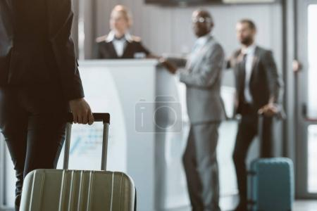 cropped shot of businesswoman with luggage walking to airport reception