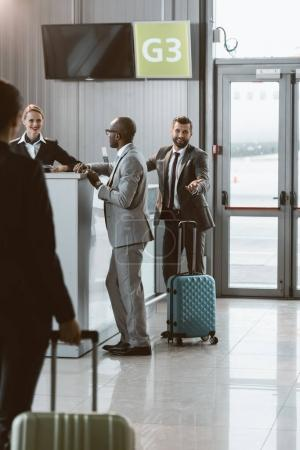 businesspeople standing at airport reception to buy tickets while colleague walking to them
