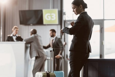 businessman looking at watch while waiting for flight at airport lobby