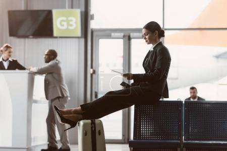 businessman looking at ticket while waiting for flight at airport lobby