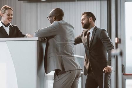 Photo pour Hommes d'affaires permanent à réception de l'aéroport le plus pratique d'acheter des billets - image libre de droit