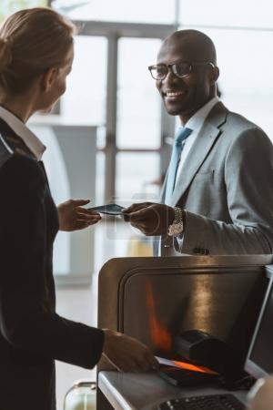 Photo pour Beau homme d'affaires souriant donnant passeport au personnel au comptoir d'enregistrement de l'aéroport - image libre de droit