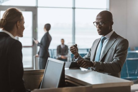 angry businessman giving passport and ticket to staff at airport check in counter