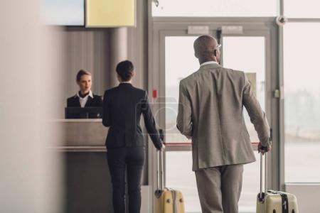 Photo pour Vue arrière des gens d'affaires marchant jusqu'au comptoir d'enregistrement de l'aéroport - image libre de droit