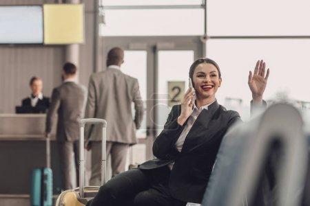 jeune femme d'affaires en attente de plan à Hall de l'aéroport tout en parlant par téléphone et agitant la main