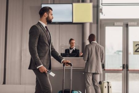 businessman with luggage and flight ticket at airport