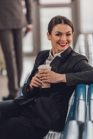 young businesswoman waiting for plane at airport and having cup of coffee to go