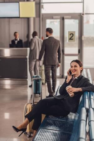 young businesswoman waiting for plane at airport lobby and talking by phone