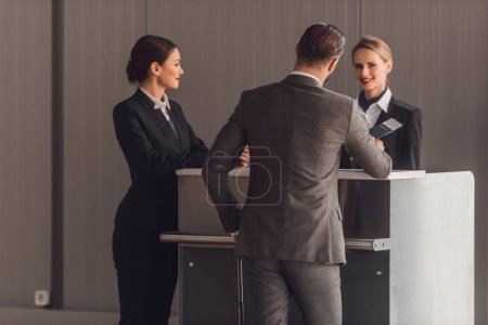 rear view of young businessman standing at airport check in counter