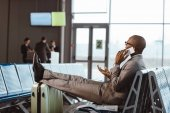 businessman talking by phone while waiting for flight at airport lobby