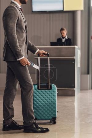 rear view of businessman with suitcase in front of airport check in counter
