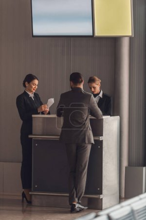 Photo pour Vue arrière de l'homme d'affaires debout au comptoir d'enregistrement de l'aéroport - image libre de droit