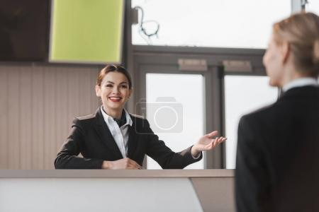 smiling attractive airport receptionist talking to client