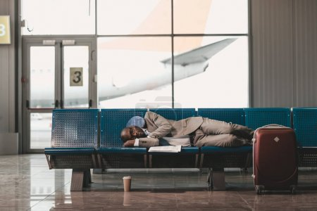 exhausted businessman sleeping on seats while waiting for flight at airport lobby