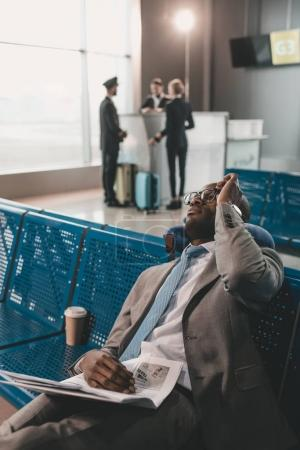 Photo for Businessman sleeping at airport lobby while waiting for flight - Royalty Free Image