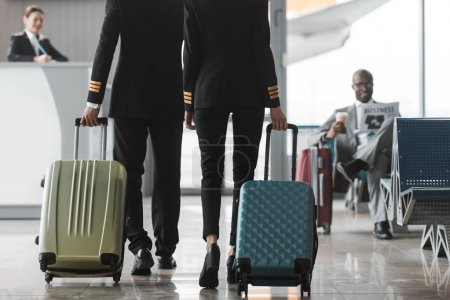 cropped shot of male and female pilots walking by airport lobby with suitcases