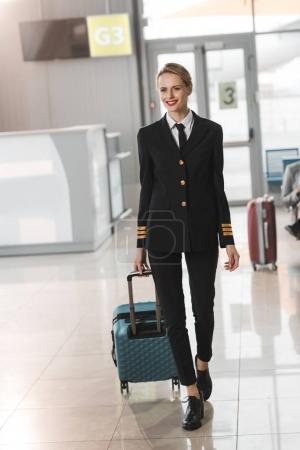 young female pilot with suitcase walking by airport lobby