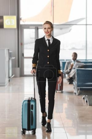 happy female pilot with suitcase walking by airport lobby