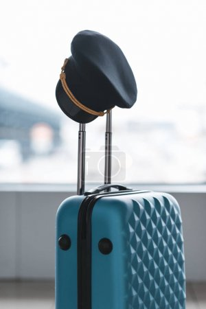pilot cap hanging on handle of suitcase at airport
