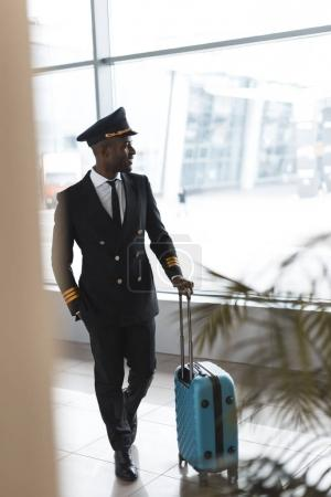 handsome young pilot in professional uniform with suitcase at airport