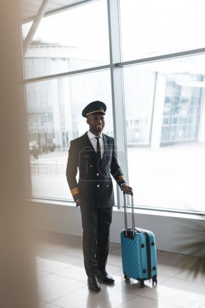 smiling young pilot in professional uniform with suitcase at airport