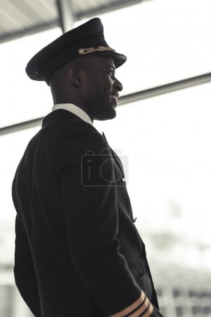 handsome young pilot looking away at airport