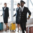Young pilot and stewardesses with luggage walking ...