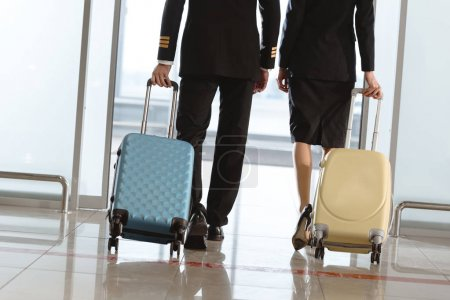 cropped shot of pilot and stewardess with suitcases walking by airport