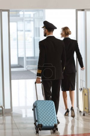 back view of pilot and stewardess walking by departure area