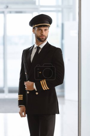 handsome young pilot in uniform at airport