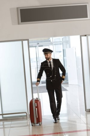 handsome young pilot with suitcase at departure area of airport