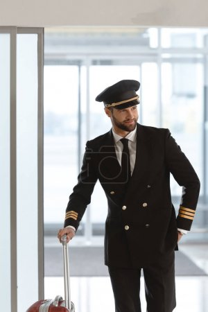 handsome young pilot with suitcase at departure area