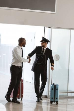 handsome pilot handshaking with young businessman at departure area of airport