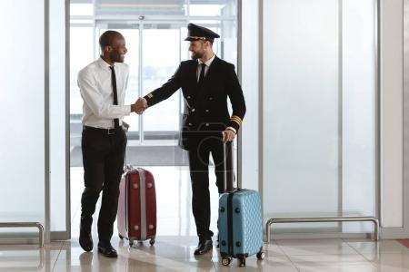 Foto de Feliz guapo piloto el apretón de manos con el joven empresario en el área de salida de aeropuerto - Imagen libre de derechos