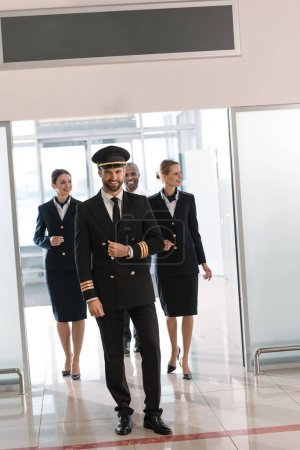 handsome young pilot walking by airport with his team