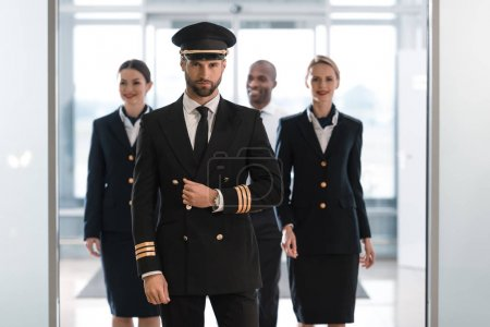 Photo for Handsome pilot at airport with his team looking at camera - Royalty Free Image