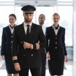 Handsome pilot at airport with his team looking at...