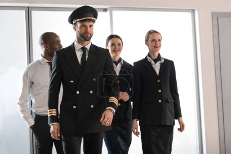 handsome pilot walking by airport with his team